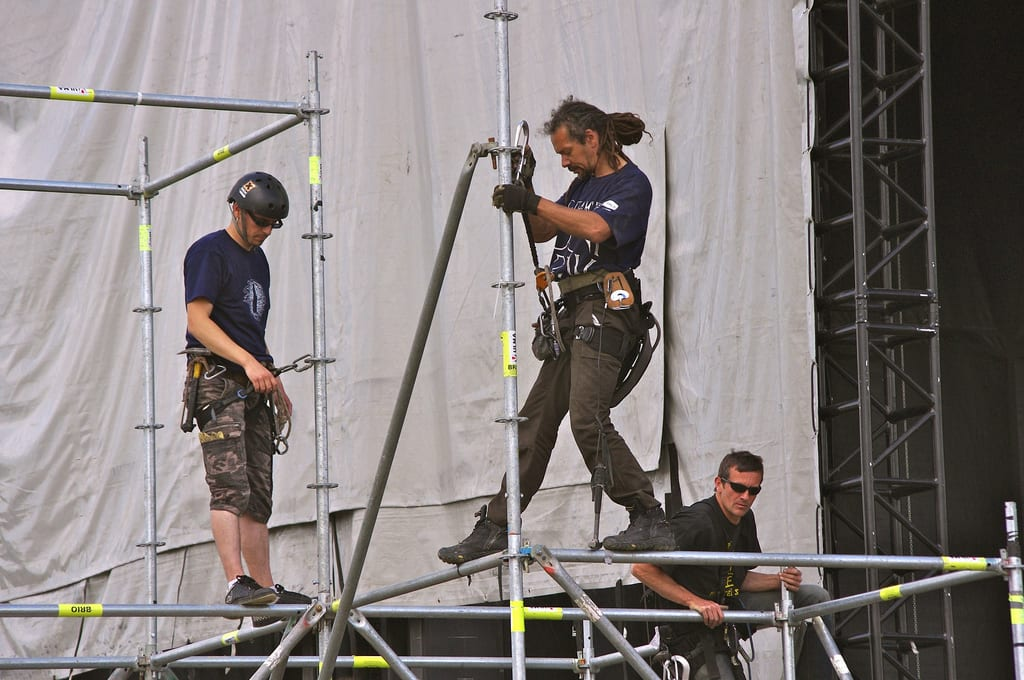 riggers working on attaching lighting and audio equipment